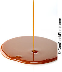 sweet caramel sauce - pouring sweet caramel sauce on a white...