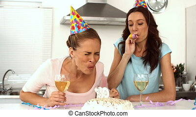 Women wearing party hats celebrating birthday together with...