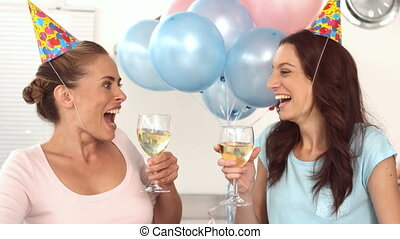 Women clinking their flutes of champagne for a birthday with...
