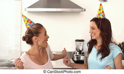 Two friends dancing together in the kitchen while wearing...