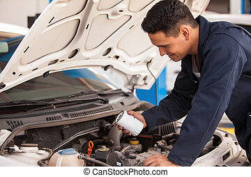 Changing the oil filter in a shop - Young Hispanic mechanic...