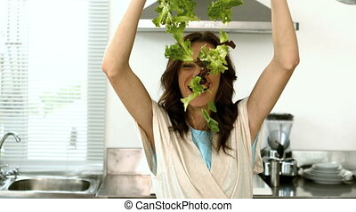 Woman lets fall lettuce while preparing a salad in the...
