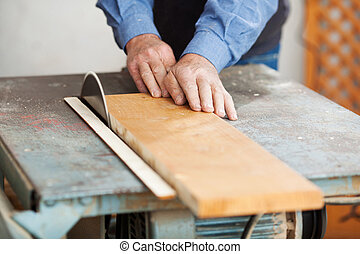 Carpenter Using Table Saw - Senior male carpenter using...
