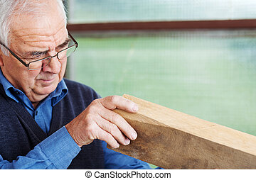Male Carpenter Analyzing Wood In Workshop - Closeup of...