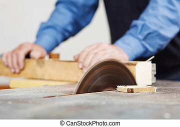 Man Using Table Saw - Senior man using table saw for cutting...