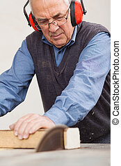 Man Wearing Ear Protectors While Using Table Saw - Senior...