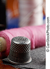 Thimble and spools of thread closeup photo