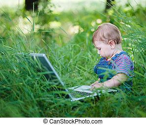 little boy with a laptop - little boy playing outdoors with...