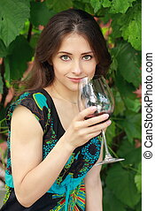 Beautiful woman drinking red wine in park on nature green...