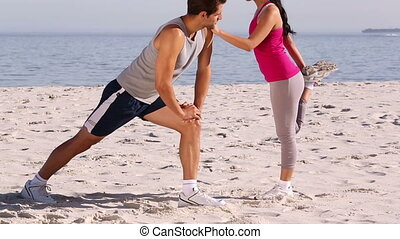 Man and woman stretching together on the beach