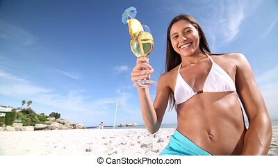 Brunette savouring a cocktail on the beach