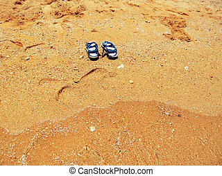 Blue summer foot wear on the yellow sand of seashore