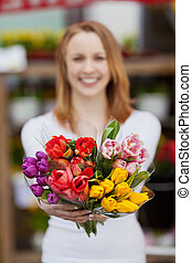Woman showing different flowers - Image of a woman standing...