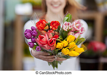 Woman showing a bunch of assorted flowers - Closeup...