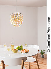 Decorative chandelier and elegant table with white wine -...