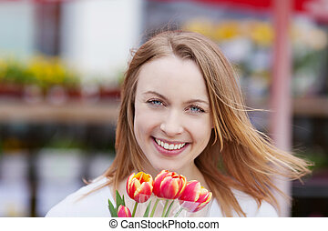 Pretty female smiling while holding fresh tulips - Portrait...