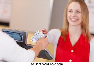 Customer paying 20 Euros to the saleswoman - Closeup shot of...