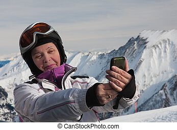 A woman photographs the skier himself smartphone