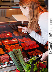 Woman purchasing meat at a delicatessen leaning forwards...