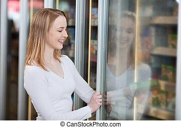 sonriente, rubio, mujer, compra, congelado, alimento