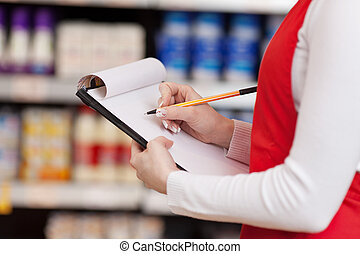 Saleswoman Writing On Clipboard In Grocery Store -...