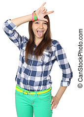 Teenage girl shows tongue and makes hand horns. Mint-colored...