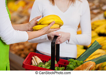 Female Worker Assisting Customer In Purchasing Bananas -...