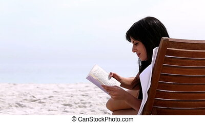 Brunette reading a book on the beach