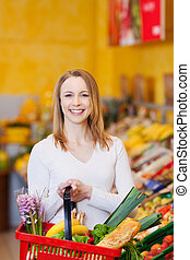Woman Carrying Shopping Basket In Grocery Store