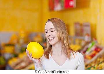 Cute young female choosing a melon to buy - Photograph of a...