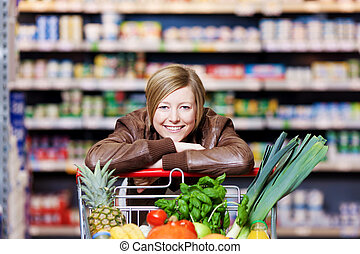 Woman with a shopping cart of fresh produce resting her chin...