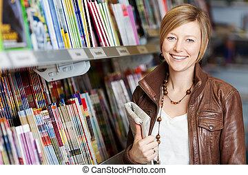 mulher, segurando, jornal, em, supermercado