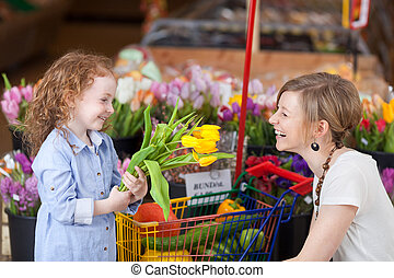 Mother and daughter buying fresh tulips