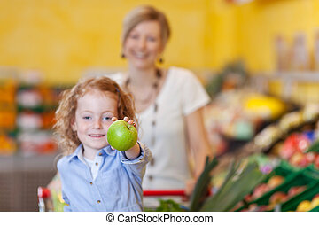 Girl Showing Apple With Mother In Background At Store -...