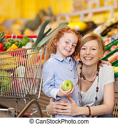 Girl Holding Apple While Mother Embracing Her In Grocery...