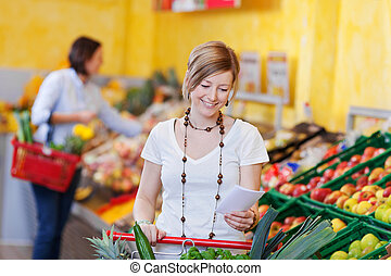 Woman with a shopping list in a supermarket standing with...