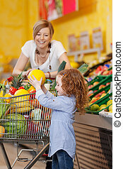 Girl Keeping Muskmelon In Shopping Cart While Mother Looking...