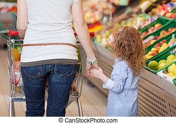 Mother holding her kids hand in supermarket - Image of a...