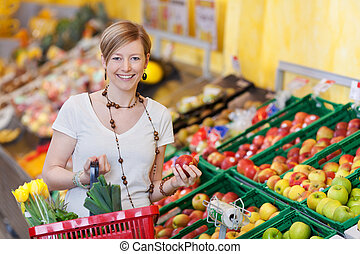Happy woman buying fresh produce in a supermarket standing...