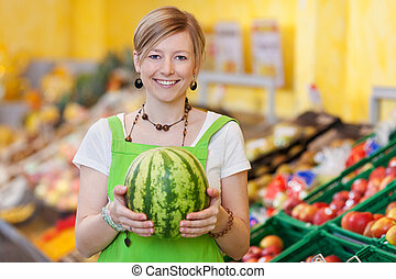 Saleswoman showing a fresh watermelon - Image of a...