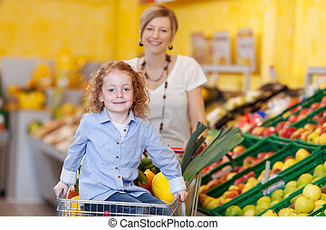 Pretty little girl and her mother in a supermarket