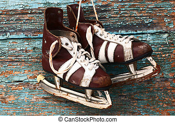 vintage pair of mens ice skates on a wooden wall - vintage...