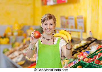 Friendly saleswoman showing different fruits - Image of a...