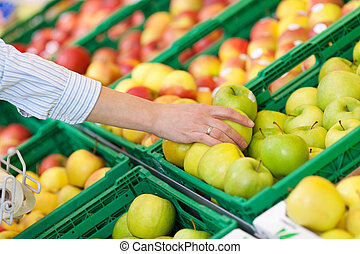 Woman buying a fresh green apple