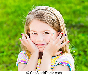 Cute smiling blond little girl with many-coloured manicure -...