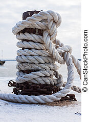 old bollard and frozen ship cable - frozen ship cable under...