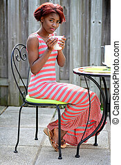 young black woman enjoying coffee on the patio