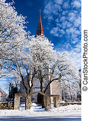 weathered catholic church on a snowy trees - winter...