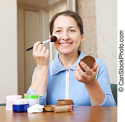 mature woman puts facepowder on her face with brush