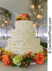 Fancy wedding cake inside a large event tent.